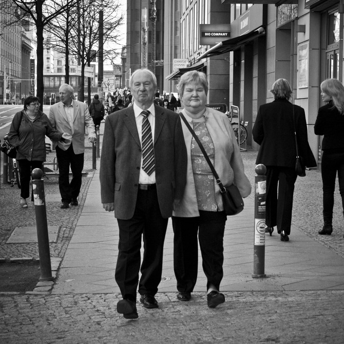 Two elderly people walk on the sidewalk.